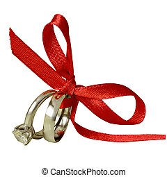 Engagement and wedding rings tied with red ribbon