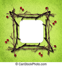 Frame made from dry twigs on green paper background