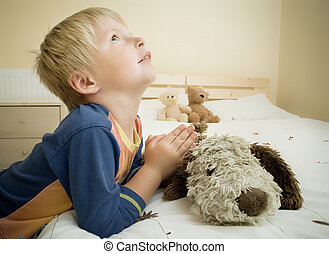 Little boy prays in the bedroom by the bed