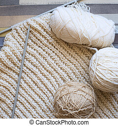 Balls of wool and knitting on a wooden table. View from above.