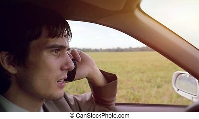 Young handsome dark-haired man driving car in the field and...