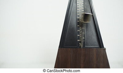 Vintage metronome, on a white background - Color shot of a...