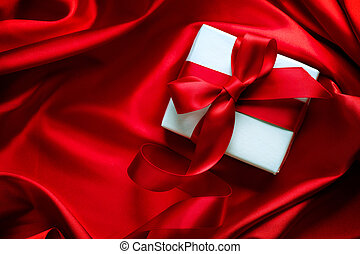 Valentine gift box with red satin ribbon on red silk...