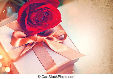 Valentine's Day. Red rose and gift with silk bow over vintage background