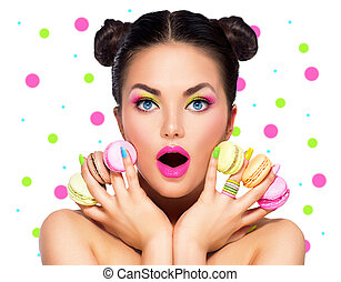 Beauty surprised fashion model girl with colourful makeup and manicure with colorful macaroons
