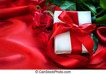Valentine's Day red roses and gift over silk background