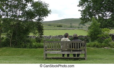 Elderly couple on bench enjoy view