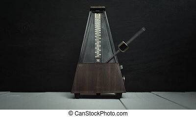 Vintage metronome, on a dark background. - Color shot of a...