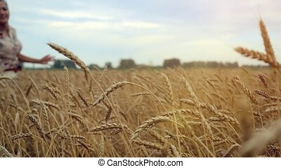 Young smiles woman running in a wheat field. Hand of a young...