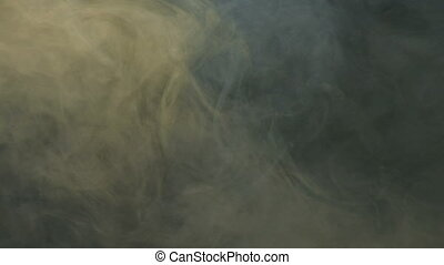 smoke slowly floating through space against black background
