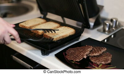 Female hand turns a light bread on an electric grill. Close-up .