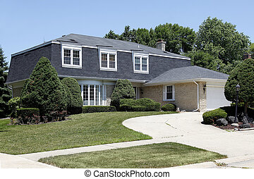 Suburban home with circular drive and brick garage