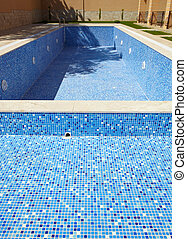 Empty swimming pool - Blue tiled empty swimming pool on a...