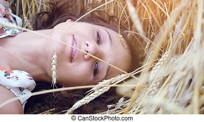 Beautiful young romantic woman with long hair lies on wheat...