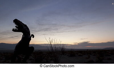4K time lapse close up desert sunrise dinosaur silhouette -...
