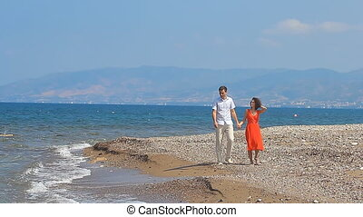 Couple walking on beach Young happy interracial couple...