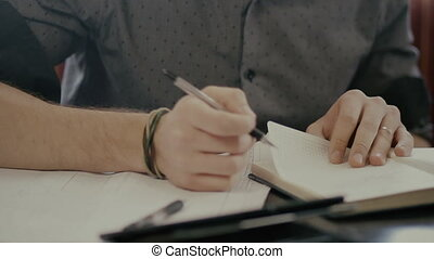 signs documents and sketches - Mans hand signs documents and...