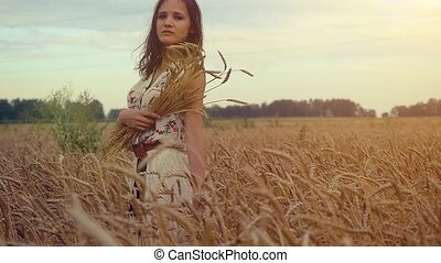 Young beautiful romantic woman walking in a wheat field. Hand of a young girl touching corn ears in a field at sunset in slowmotion. hd, 1920x1080
