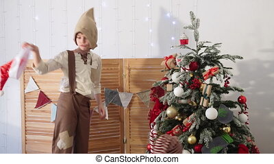 Children playing by Christmas tree, boy throws hat and...