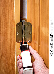 Showing how to properly oil a door hinge - Demonstrating a...