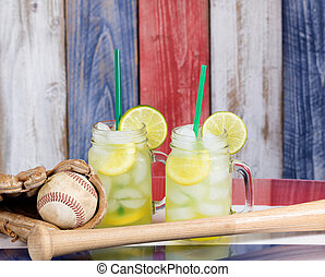 Glass jars filled with cold lemonade along with baseball...