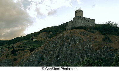 An old fortress with flags on the mountain. It's located in...