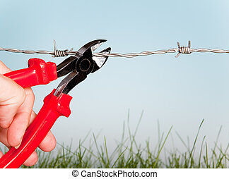 Cutting barbed wire - Hand cutting barbed wire with pair of...