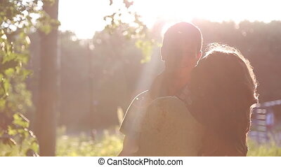 Young couple embracing at sunset - Rear view of an...