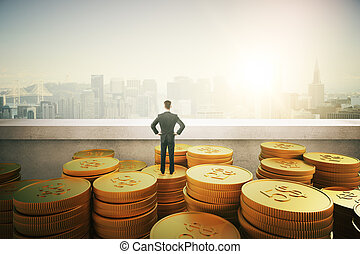 businessman standing on gold coins and looking on city