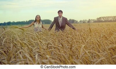 Handsome man and beautiful woman holding hands and running on wheat field in slowmotion. 1920x1080. hd