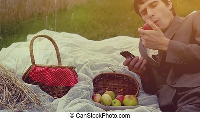 Young handsome businessman having picnic in the park. Man uses mobile phone with basket full of apples. hd, 1920x1080