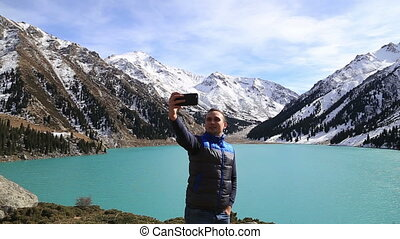 young successful white caucasian man making selfie on the background of beautiful fantastic mountain winter landscape