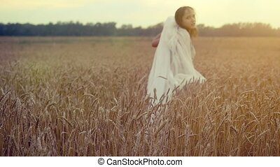 Woman walking in a wheat field Hand of a young girl touching...