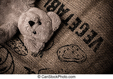 Teddy bear lying on burlap labeled vegetables - Teddy bear...