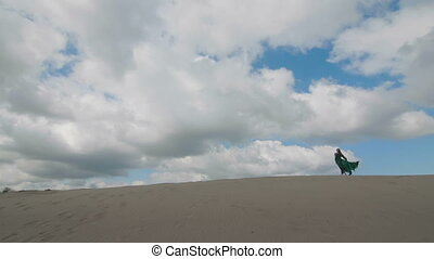 Girl stand in green dress on sand dune while wind blowing...
