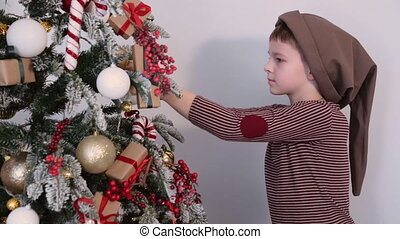 Boy in the hat dresses up Christmas tree toys - The boy in...