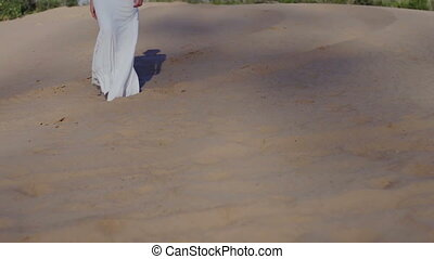 Feet of woman walking on beach dunes in white dress while sun drops shadow slow motion front view