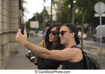 Cheerful friends taking photos of themselves on smart phone