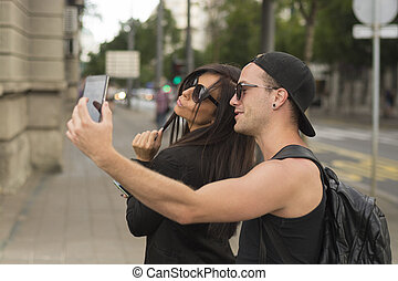 Two cheerful friends taking photos of themselves on smart phone