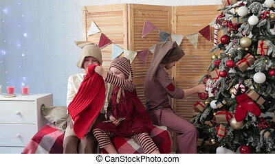 Children sit by the Christmas tree and play - The children...