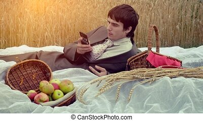 Young handsome businessman having picnic in the park. Man talking by mobile phone with basket full of apples. 4k