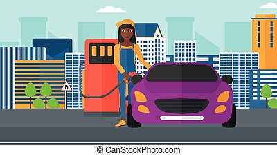 Woman filling up fuel into car - An african-american woman...