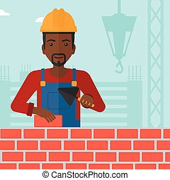Bricklayer with spatula and brick. - An african-american...