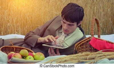 Young handsome businessman use tablet on a picnic in wheat...
