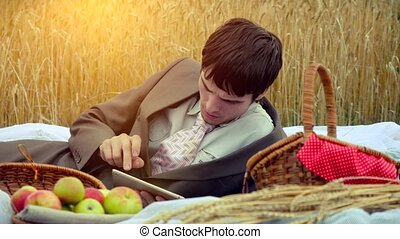 Young handsome businessman use tablet on a picnic in wheat field. 4k