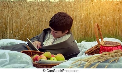 Young handsome businessman use tablet on a picnic in wheat field. 1920x1080