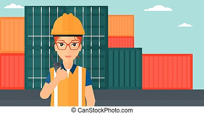 Stevedore standing on cargo containers background - A woman...