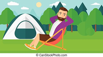 Man sitting in folding chair. - A hipster man with the beard...