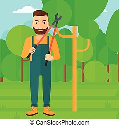 Farmer with pruner in garden - A hipster man with the beard...
