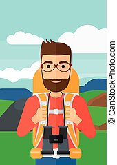 Cheerful backpacker with binoculars - A hipster man with...